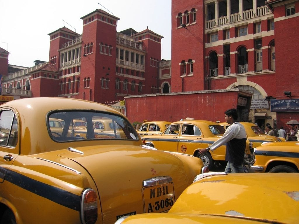 The famous Ambassador taxis waiting outside a train station in Culcatta, India