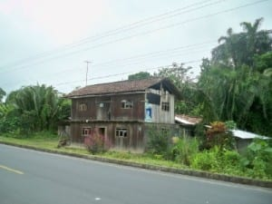 Passing a ramshackle looking two storey board house in Ecuador