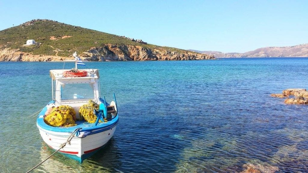 A boat floating in a quiet bay in Patmos, Greece