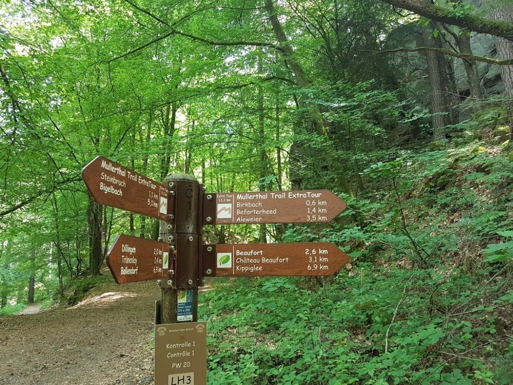 A signpost marking the Mullerthal Trail in Luxembourg along with some other local routes