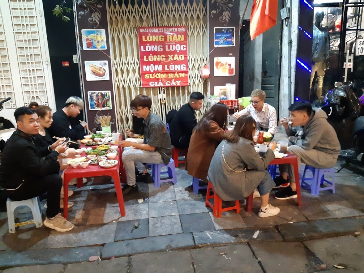 Eating street food in Hanoi whilst sitting on the small plastic chairs and tables.