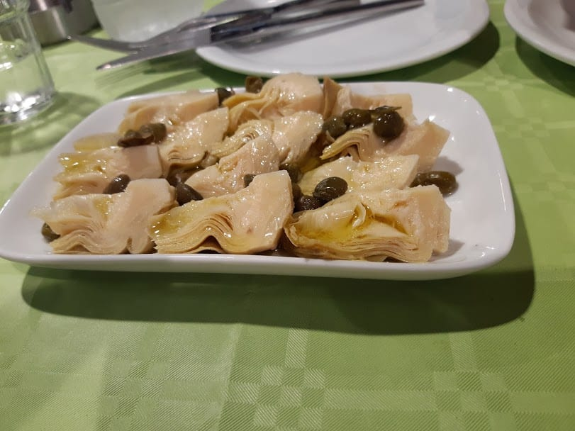 Eating marinated artichokes in Tinos island Greece