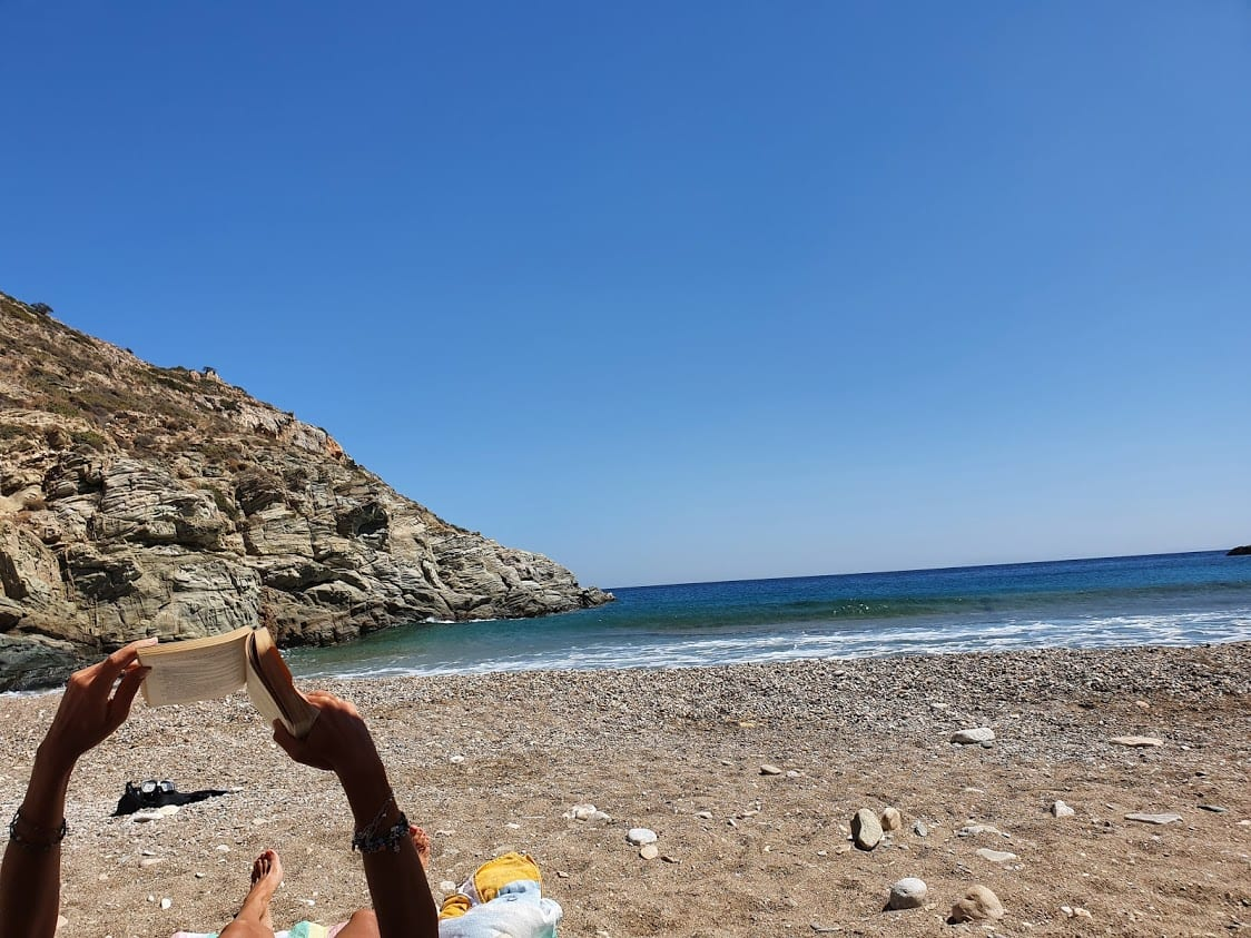 Reading a book on the beach in Sikinos Greece