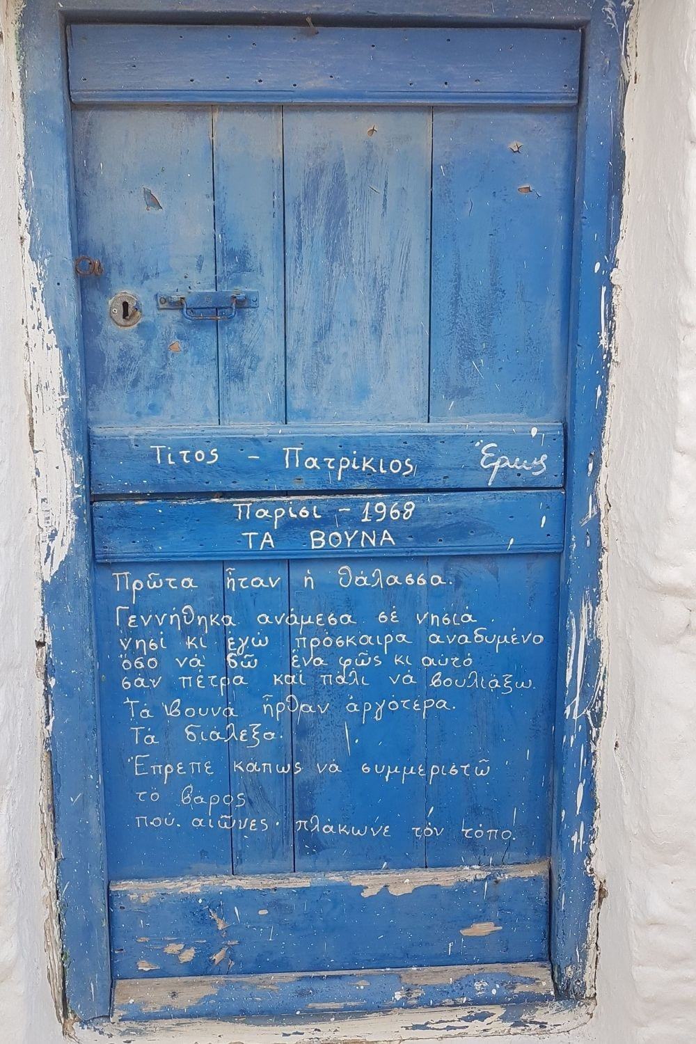 A door with Greek poetry written on it as seen in Tinos island in Greece