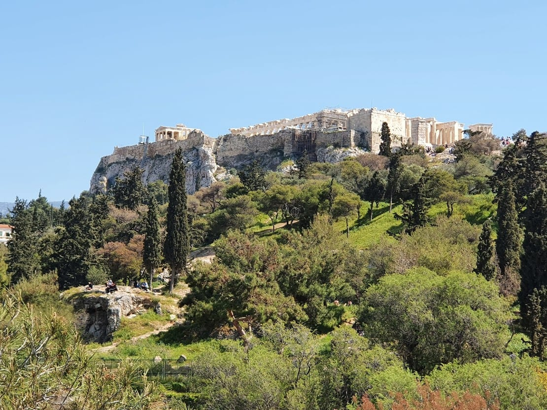 The Acropolis of Athens surrounded by greenery on a spring day