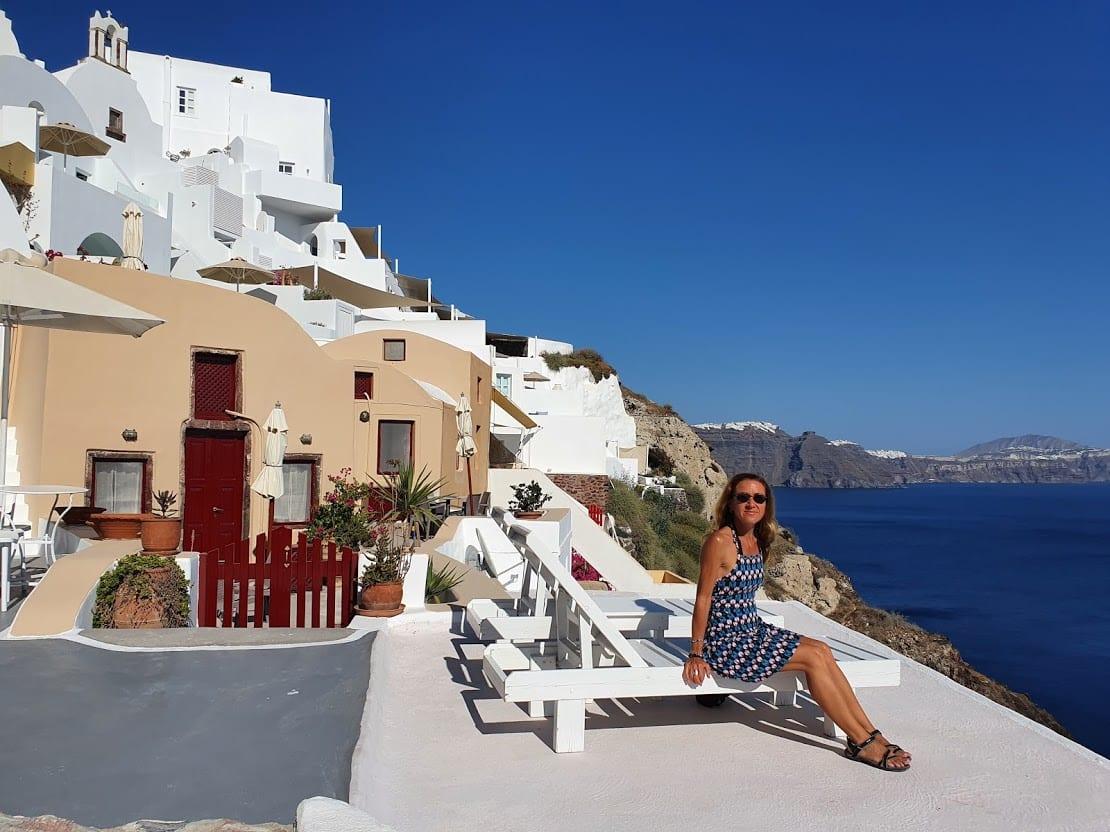 Vanessa sitting at a romantic setting in Santorini Greece